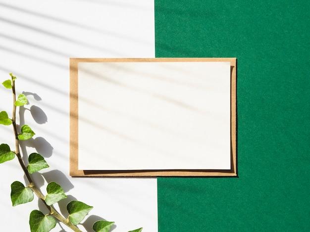 Witte en groene achtergrond met een witte deken en een groene tak met schaduw Gratis Foto