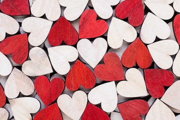 Witte en rode harten, achtergrond met houten harten. Premium Foto