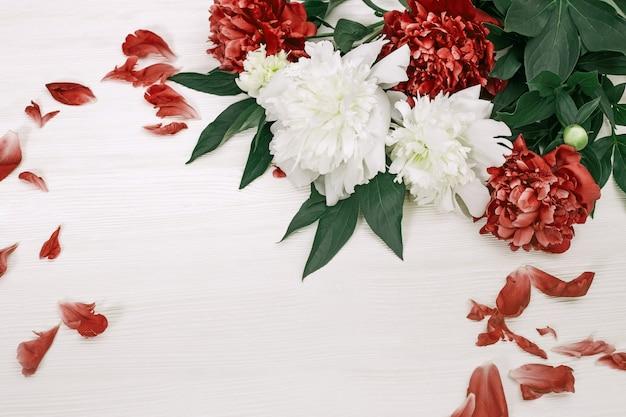 Witte en rode pioenrozen met gevallen bloemblaadjes op wit hout Premium Foto