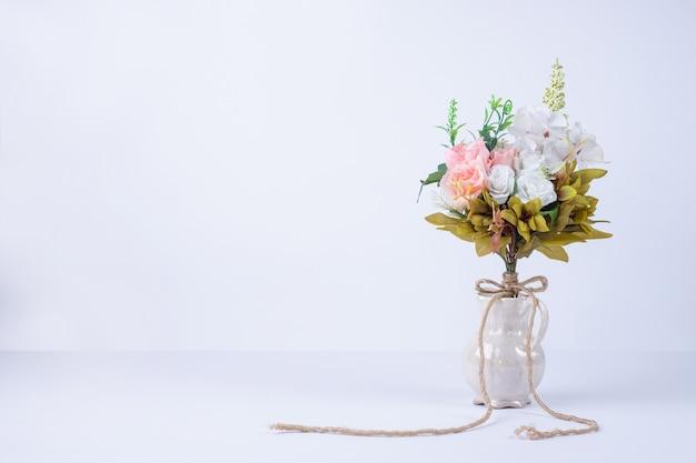 Witte en roze bloemen in keramische vaas op wit. Gratis Foto
