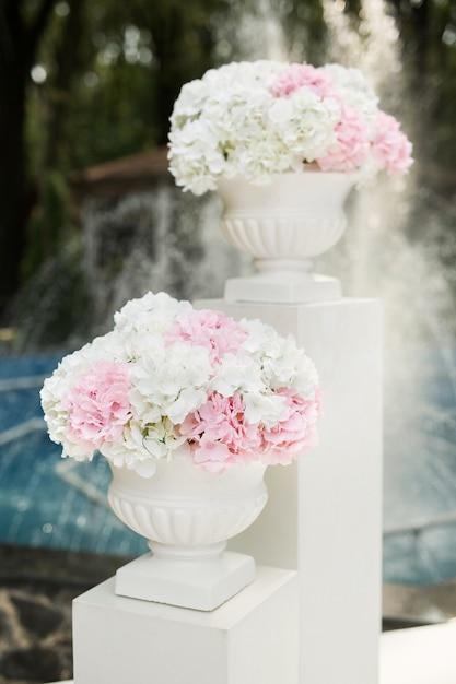 Witte en roze bloemen in vazen tijdens de huwelijksceremonie Premium Foto