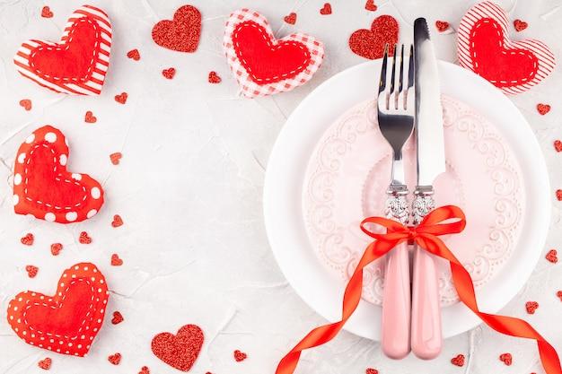 Witte en roze borden met vork, mes en rode strik met decoratieve harten Premium Foto