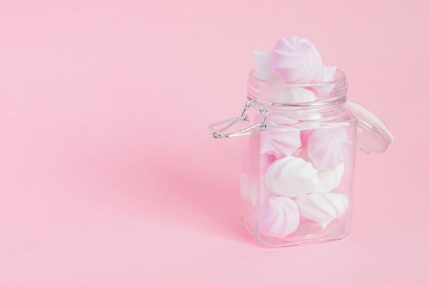 Witte en roze gedraaide schuimgebakjes in een glazen pot op roze Premium Foto