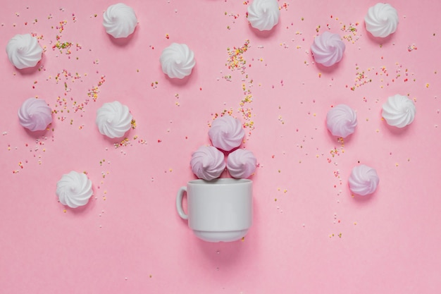 Witte en roze gedraaide schuimgebakjes in porseleinen kom en kleurrijke bogen op roze Premium Foto