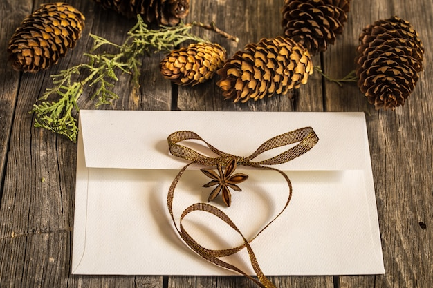 Witte envelop op houten muur met dennenappels en kerstcadeau Gratis Foto