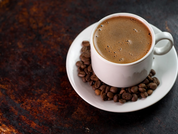 Witte espressokop op roestige ijzer bruine achtergrond met koffiebonen Premium Foto
