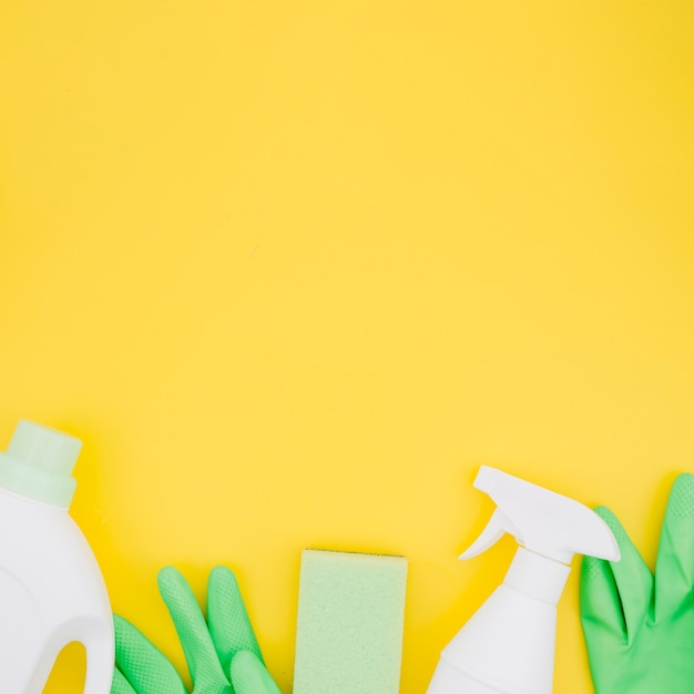 Witte flessen met groene handschoenen en spons op gele achtergrond Gratis Foto