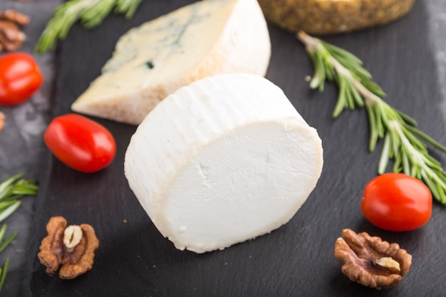Witte geitenkaas en diverse soorten kaas met rozemarijn en tomaten Premium Foto