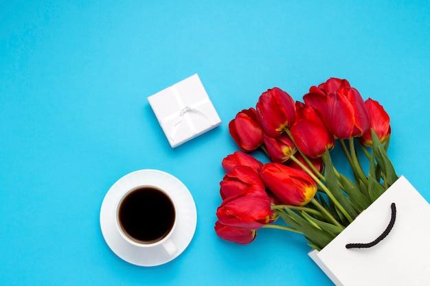 Witte geschenktas, een kleine witte geschenkdoos, een witte kop met zwarte koffie en een boeket rode tulpen op een blauwe. concept biedt een verloving of huwelijk, winkelen Premium Foto