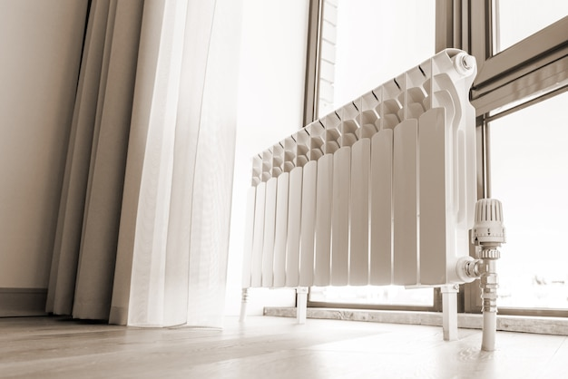 Witte grote radiator dichtbij venster in moderne ruimte, sepia het stemmen Premium Foto