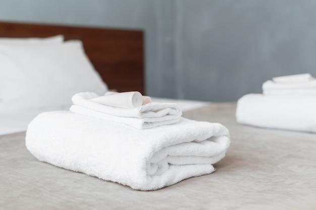 Witte handdoek op bed in logeerkamer voor hotelklant Premium Foto