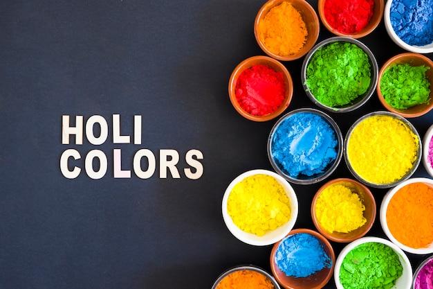 Witte holi kleurt tekst dichtbij het holikleurpoeder in de kom tegen zwarte achtergrond Gratis Foto