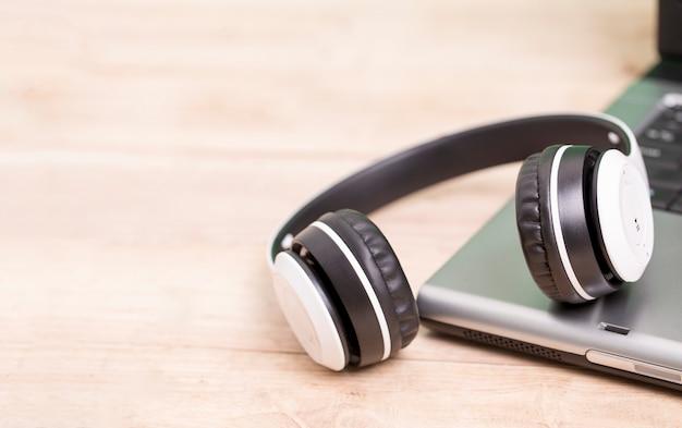 Witte hoofdtelefoons die op computerlaptop worden geplaatst op de lijst Premium Foto