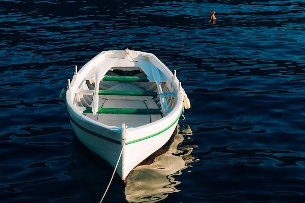 Witte houten boot met roeiriemen vissen op het blauwe water van de baai van kotor in montenegro. Premium Foto