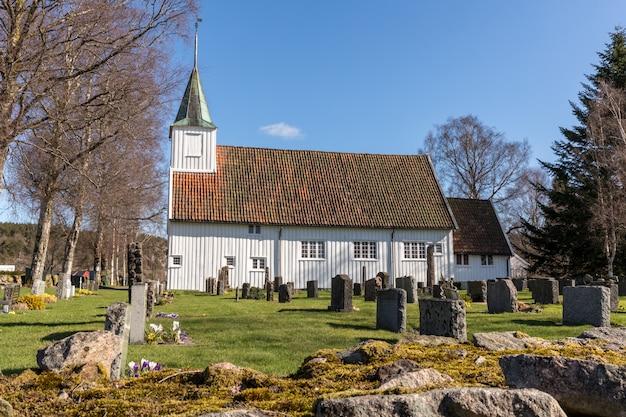 Witte houten kerk in sogne, een parochiekerk in sogne, vest-agder in noorwegen. blauwe lucht, groen gras. Premium Foto