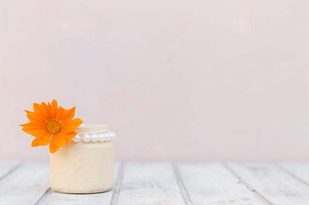 Witte houten oppervlak met vaas en oranje bloem Gratis Foto