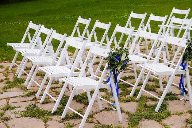Witte houten stoelen versierd met bloemen en heldere satijnen linten, bruiloft decor tijdens de ceremonie. Premium Foto