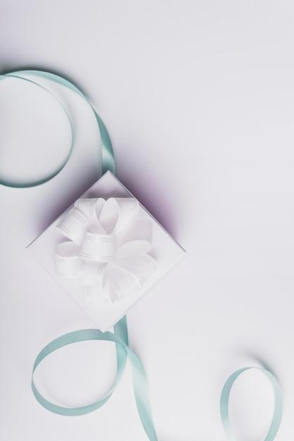 Witte huidige doos met gekruld turkoois lint dat op witte achtergrond wordt geïsoleerd Gratis Foto