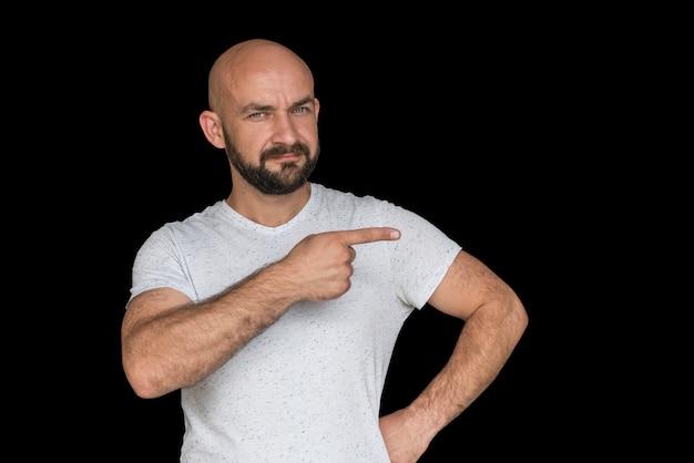 Witte kale man met een baard in een wit t-shirt wijst met de vinger naar de zijkant Premium Foto