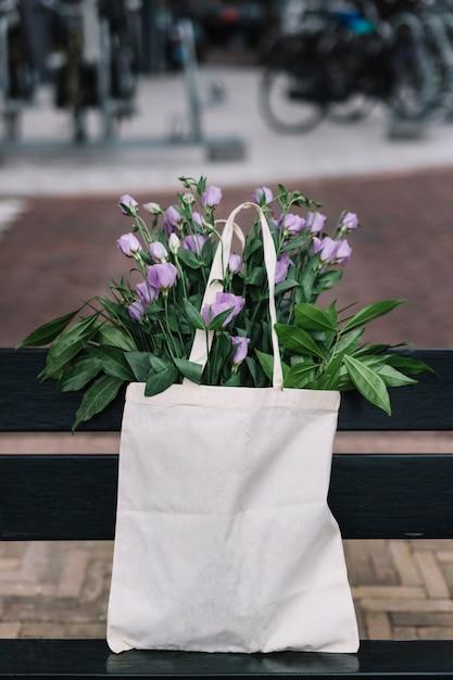 Witte katoenen handtas met prachtige paarse eustoma bloemen Gratis Foto