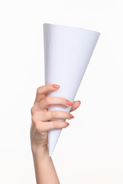 Witte kegel van de rekwisieten in de vrouwelijke handen op witte achtergrond met juiste schaduw Gratis Foto
