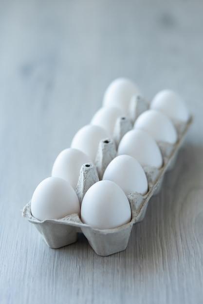 Witte kippeneieren in een open milieuvriendelijke kartonnen doos Premium Foto