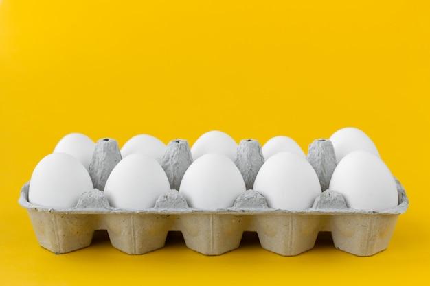 Witte kippeneieren in open kartonkarton op gele achtergrond Premium Foto