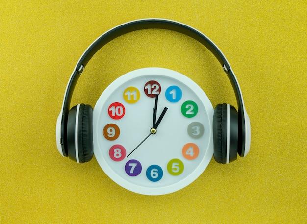 Witte klok met hoofdtelefoon op mooie gouden kleurenachtergrond Premium Foto