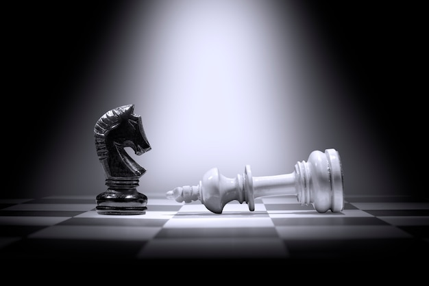 Witte koning schaakstuk verslaan door zwarte ridder schaakstuk Premium Foto