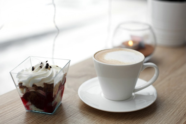 Witte kop hete cappuccino op witte schotel en rood fluweeldessert op houten barlijst naast venster Premium Foto