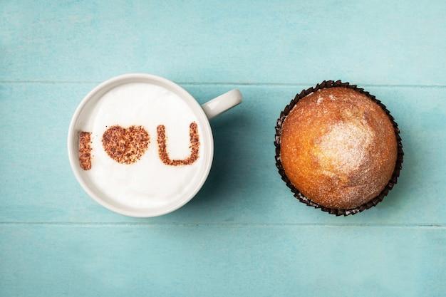 Witte kop koffie met het opschrift op het schuim ik hou van je en een cupcake. Premium Foto