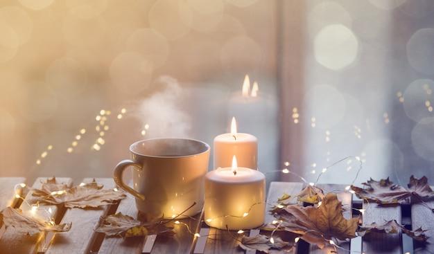 Witte kop koffie of thee in de buurt van kaarsen met esdoorn bladeren Premium Foto