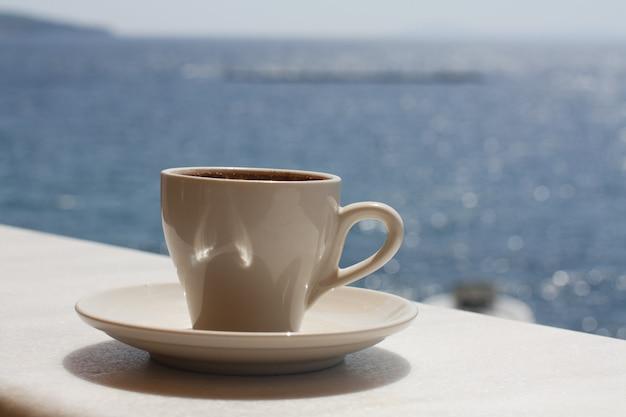 Witte kop met koffie op de achtergrond van de zee. zonnige dag, vakantie op zee. genot moment. genieten van een kopje koffie aan zee. Premium Foto