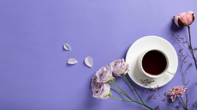 Witte kop met zwarte koffie en delicate lila rozen, gedroogde bloemtakken op een lila achtergrond. creatief ontbijt. plat lag stijl, banner, kopie ruimte Premium Foto