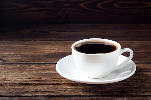 Witte kop met zwarte koffie op houten tafel Premium Foto
