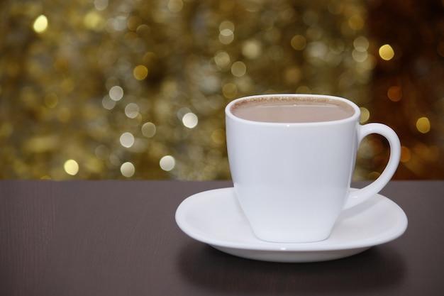 Witte kopje koffie met melk, glinsterende bokeh lichten. vieren, kerstmis, nieuwjaar, vakantie partij achtergrond. Premium Foto