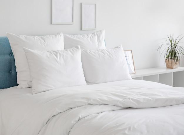 Witte kussens en dekbed op het blauwe bed. Premium Foto