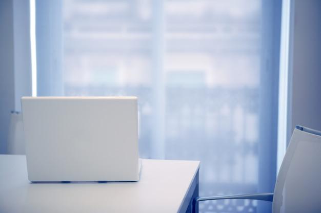 Witte laptop open op een witte ruimte, blauw licht dat uit venster komt Premium Foto