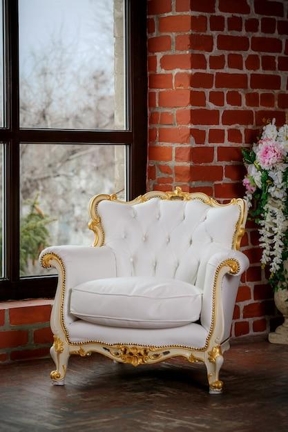 Witte lederen fauteuil in de buurt van venster Premium Foto