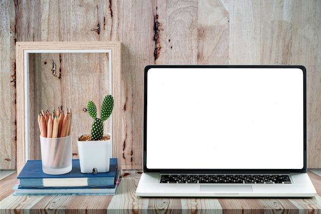 Witte leeg scherm laptop, houten fotolijst en groene cactus bloem op houten tafel. Premium Foto