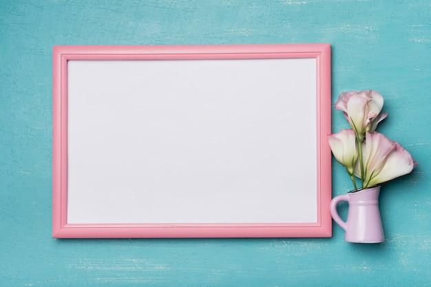 Witte lege afbeeldingsframe met roze rand en vaas op blauwe achtergrond Gratis Foto