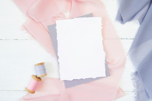 Witte lege kaart op een achtergrond van roze en blauwe stof op wit Premium Foto