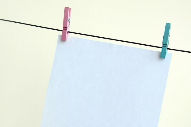 Witte lege kaarten op touw, lichte muur achtergrond. Premium Foto