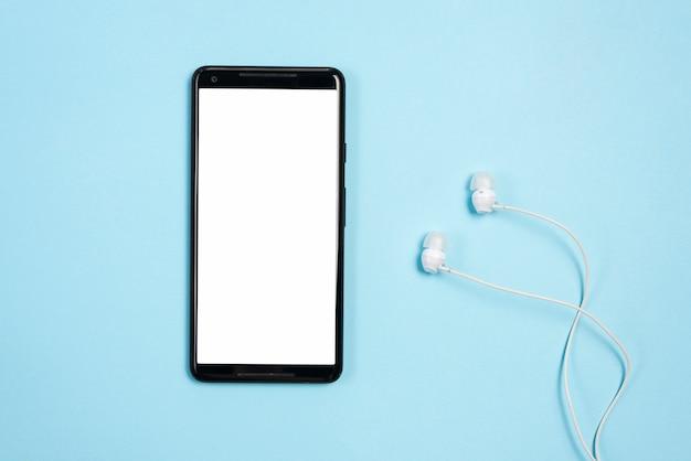 Witte lege scherm op mobiele telefoon met oortelefoons tegen blauwe achtergrond Gratis Foto