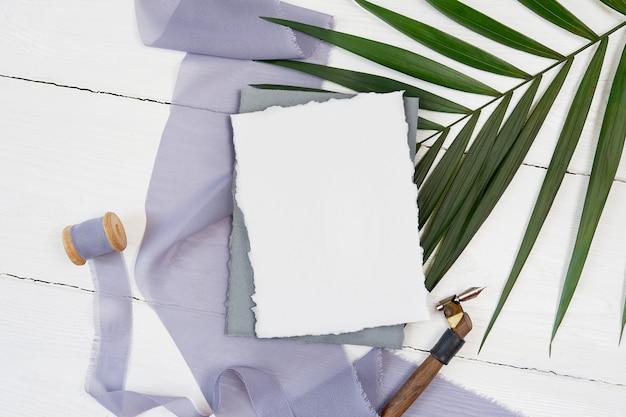 Witte lege wenskaart en grijs lint met palmblad en kalligrafische pen Premium Foto