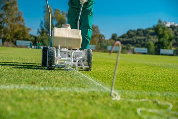 Witte lijnen op het voetbalveld getekend met witte verf op het gras met behulp van een speciale machine voor een wedstrijd Premium Foto