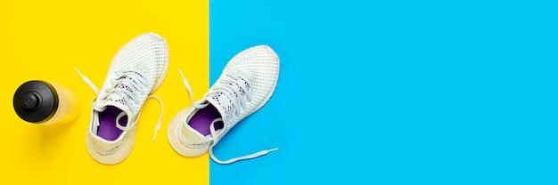 Witte loopschoenen en een fles water op een abstracte gele en blauwe ondergrond. concept van hardlopen, training, sport. . plat lag, bovenaanzicht Premium Foto