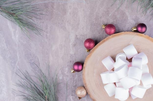 Witte marshmallows op een houten bord met rond kerstballen. Gratis Foto