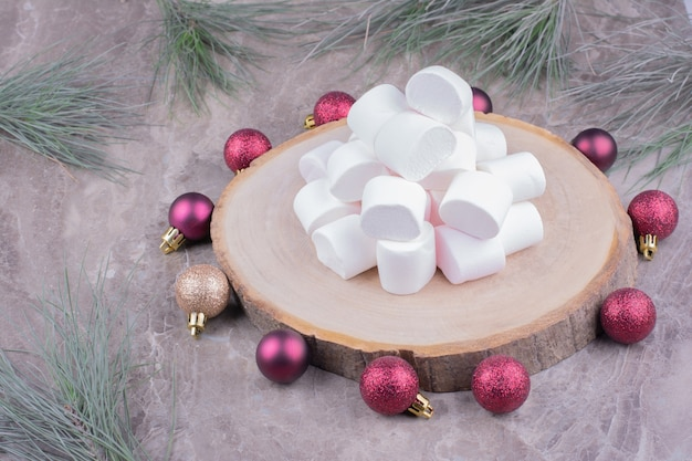 Witte marshmallows op een houten schotel met rode kerstballen rond Gratis Foto