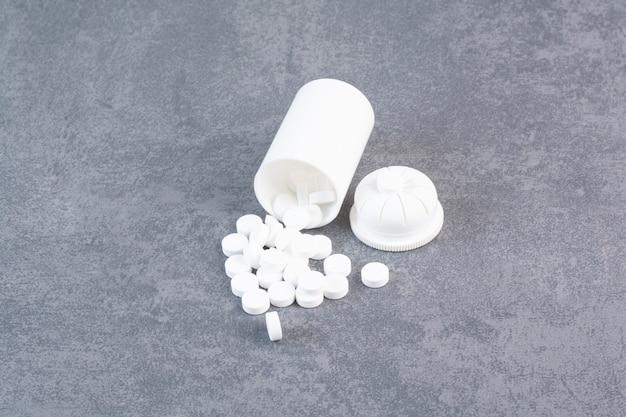 Witte medische pillen uit plastic container. Gratis Foto